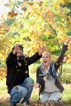 to crouch: joyful couple playing with dead leaves in autumn Stock Photo