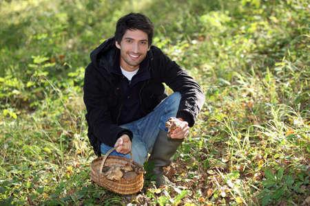 Young man picking wild mushrooms Stock Photo - 14101560