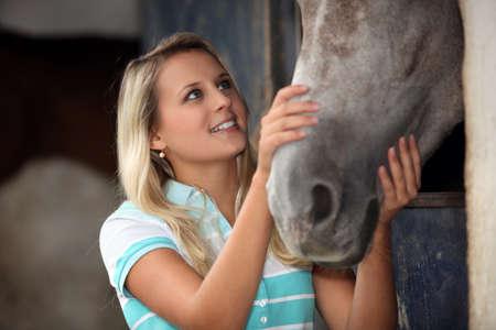 Teen stroking horse photo
