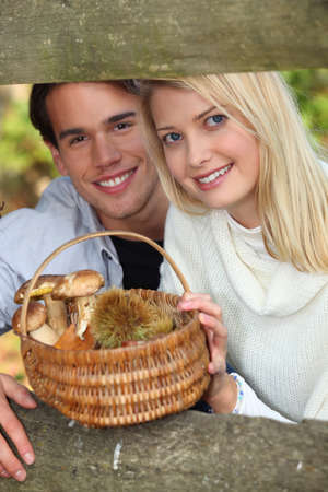 Couple collecting mushrooms and chestnuts in the forest photo