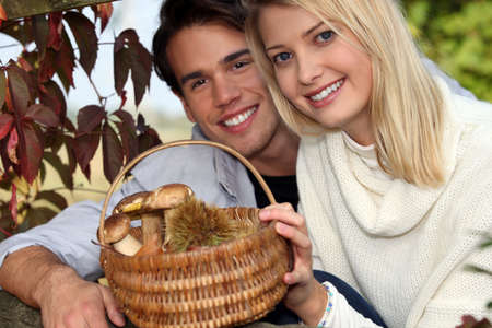 Couple collecting chestnuts and mushrooms in the forest photo