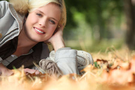 encouraged: Blonde woman on a bed of dry leaves