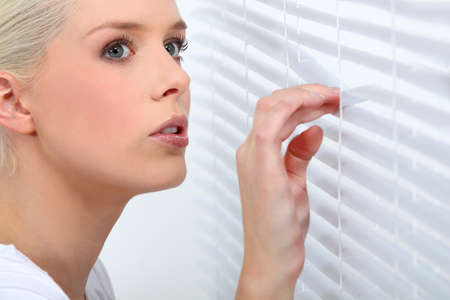 spy girl: Woman looking through venetian blinds