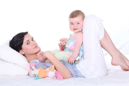 baby with soother: Woman lying in bed with baby Stock Photo