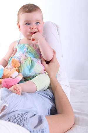 stuffed toy: mother resting baby on knees Stock Photo