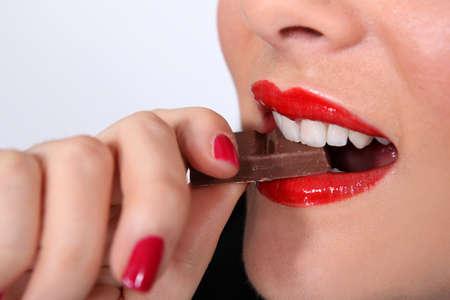 woman bar: woman eating chocolate Stock Photo