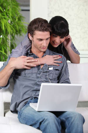 Couple listening to a laptop on headphones photo
