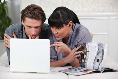 real estate planning: Couple looking at a brochure and a laptop