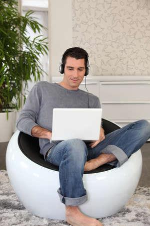 piedi nudi ragazzo: L'uomo l'ascolto di musica tramite computer portatile Archivio Fotografico