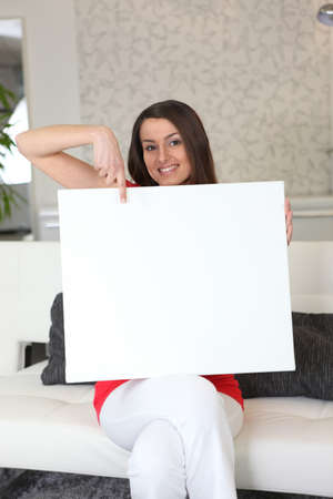 particularly: Woman sitting on sofa pointing white panel Stock Photo