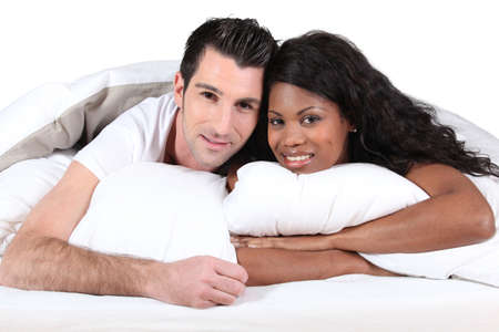 Man and woman smiling laid in a bed photo