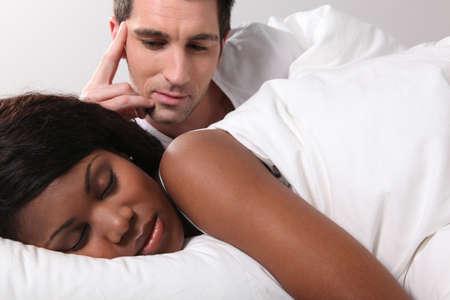 mixed couple: Man watching his girlfriend sleep