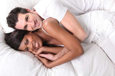 curare teneramente: coppia interrazziale sul letto