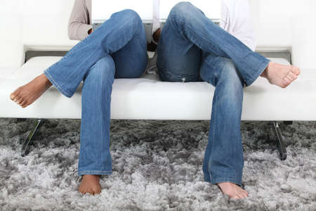 Legs crossed of couple sitting on sofa photo