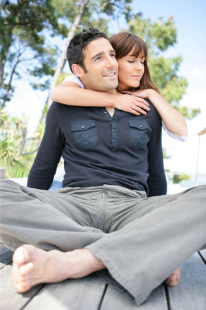 barefoot man: Man sitting cross-legged and being hugged by his wife