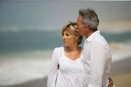 older couples: Married couple dressed in white taking a walk along the beach Stock Photo