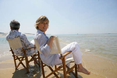 Couple sitting in chairs at the edge of the beach photo