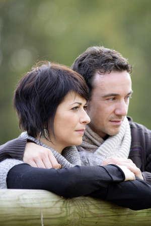 Couple stood by  fence photo