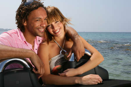 Young couple at the beach stood by convertible car photo