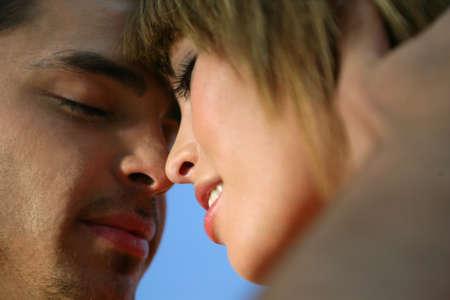 romantic sky: Couple kissing against a blue sky Stock Photo