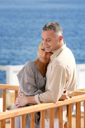 Middle aged couple stood on balcony overlooking the sea photo