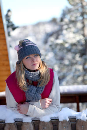 Woman stood on porch of winter chalet photo