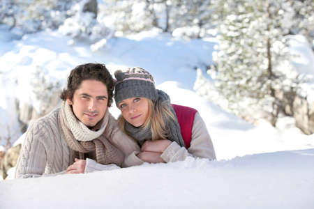 Couple laying on snowy hillside photo