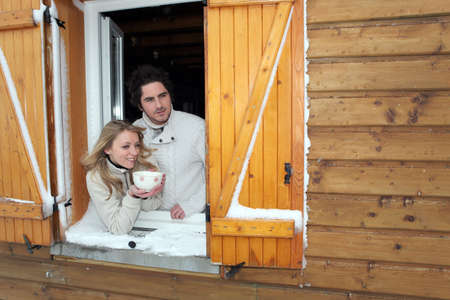 Couple looking out of their winter cabin photo