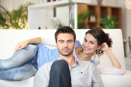 lying on couch: Couple watching television