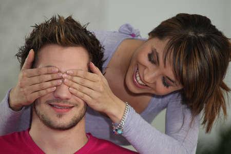 teasing: Woman covering boyfriends eyes Stock Photo