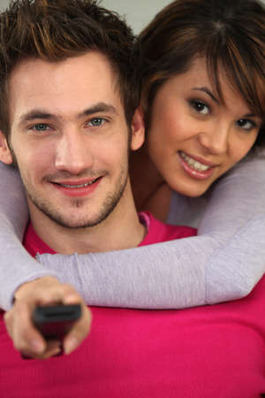 Couple with a remote control Stock Photo - 14116931