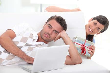 Woman surprising boyfriend with gift photo