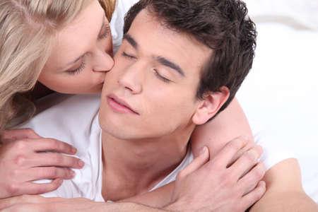 Vrouw kussen haar vriendje op de wang Stockfoto