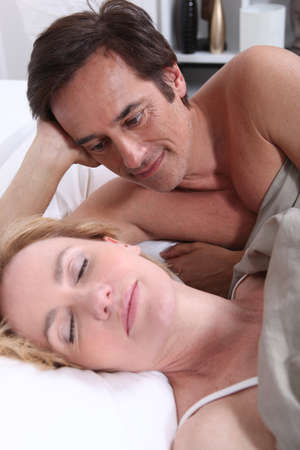 recovery position: Man watching woman sleeping Stock Photo