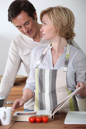 Couple in the kitchen with recipe book photo