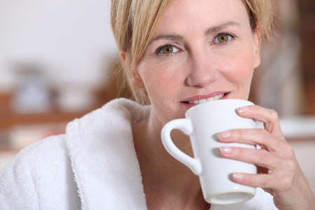 bath gown: Woman drinking a cup of tea Stock Photo