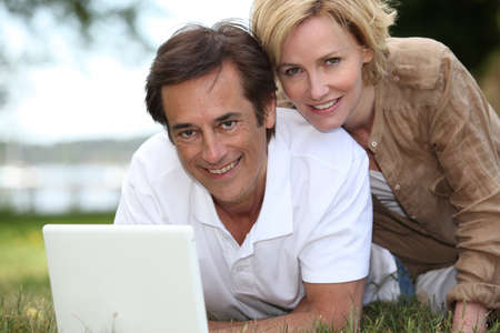 Couple on grass with computer photo
