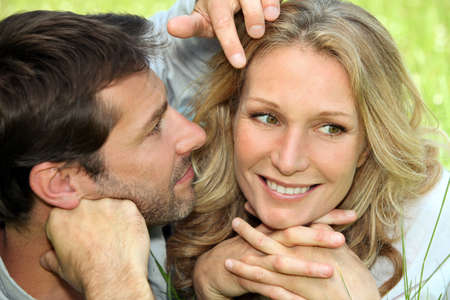 close in: Couple in love lying in the grass Stock Photo