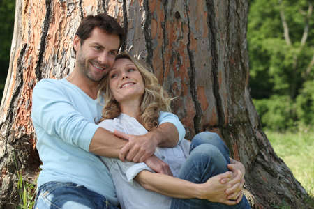 mid adult couple: Couple sitting against a tree Stock Photo
