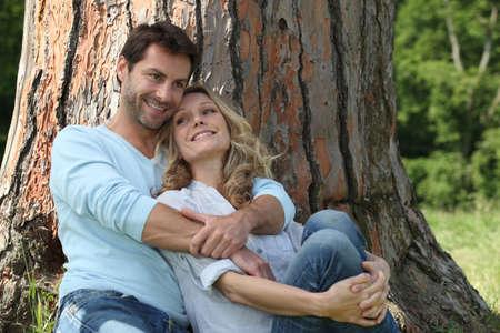 marido y mujer: Pareja sentada contra un árbol Foto de archivo