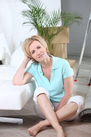 Woman sitting crossed legs on floor of new home photo