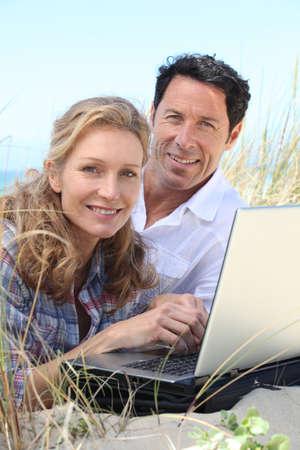 Couple smiling on laptop. photo