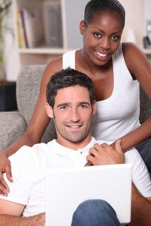 proximity: Couple sitting on sofa gray Stock Photo