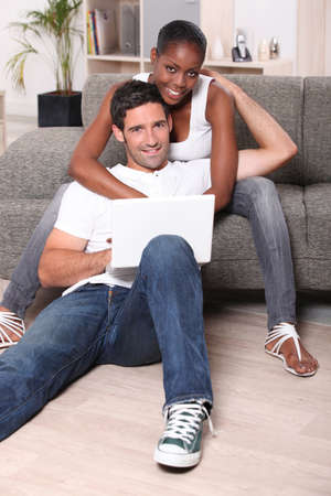 interracial love: happy couple on the sofa