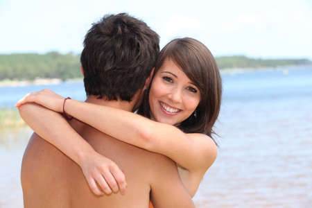 arms around: young woman hugging boyfriend at beach