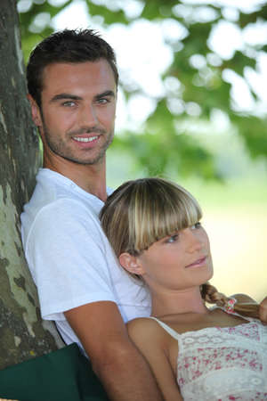 under tree: couple relaxing under a tree Stock Photo
