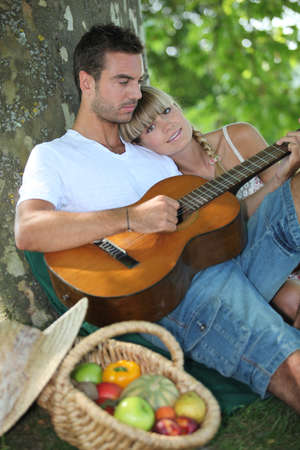 Woman beat guitar: Couple with guitar in the field
