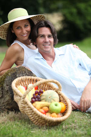 Couple posing with a fruit basket photo