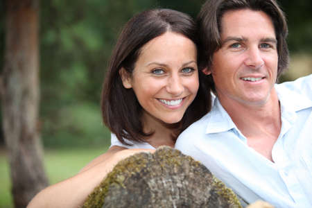 Couple leaning on tree trunk photo