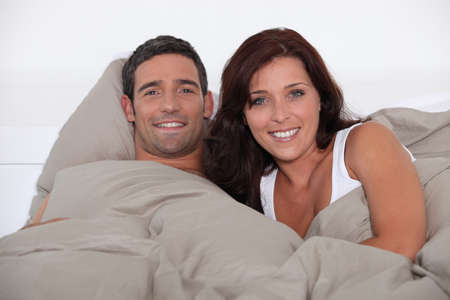 A man and woman lying in bed photo